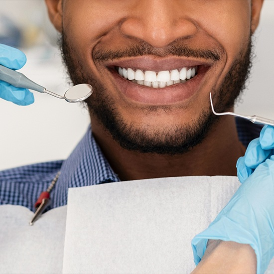 Man smiling with gum disease treatment tools by his mouth