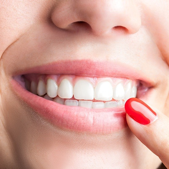 Woman pointing to smile after periodontal therapy