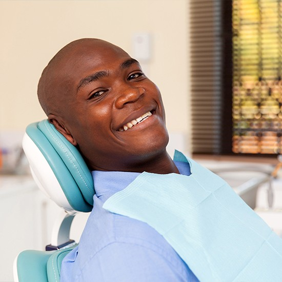 Man laying back in exam chair for dental checkup