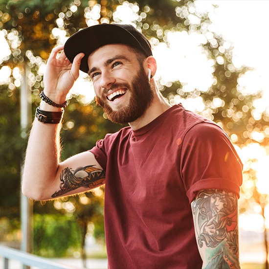 Man with tattoos smiling after root canal therapy