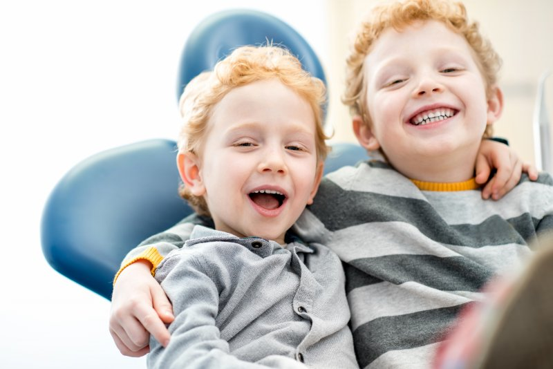 two little red-headed boys smiling in the dentist's chair