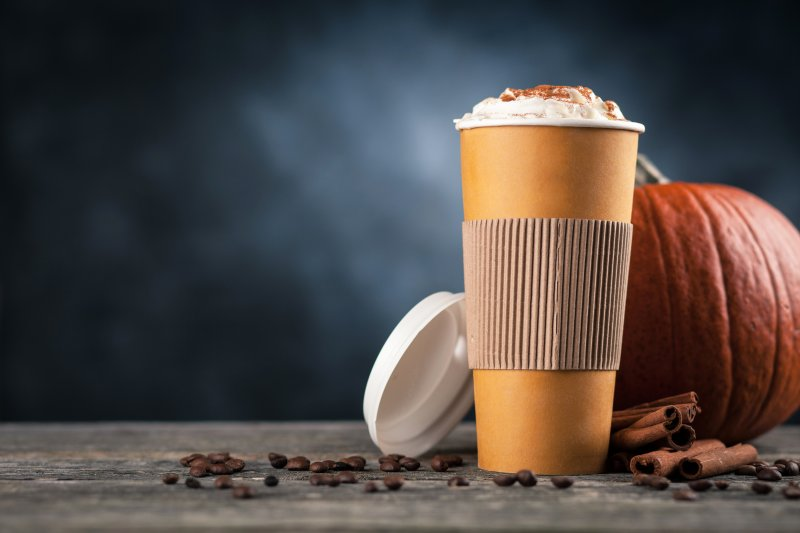 an image of a pumpkin spiced latte with the lid off and a pumpkin behind it on a table