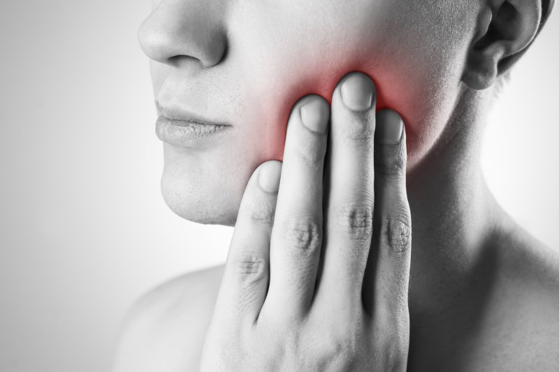 Person with inflamed TMJ considering a visit to a dentist.