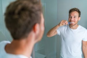 Man wearing a white t-shirt is standing in mirror brushing his teeth